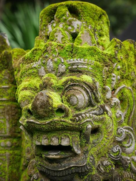 Rakasa balinesische steinskulptur bedeckt mit moos. Premium Fotos