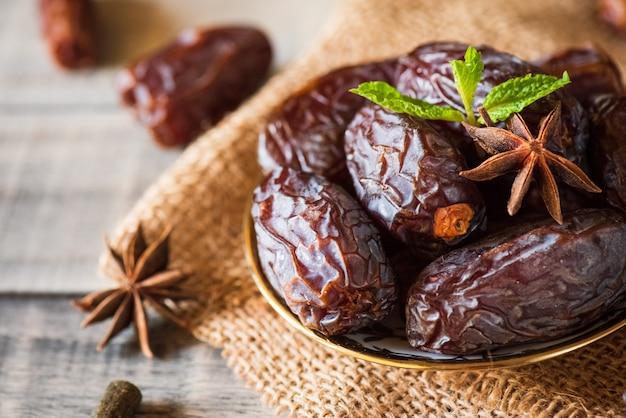 Ramadan food-konzept. datteln obst und grüne minze in einer schüssel Premium Fotos