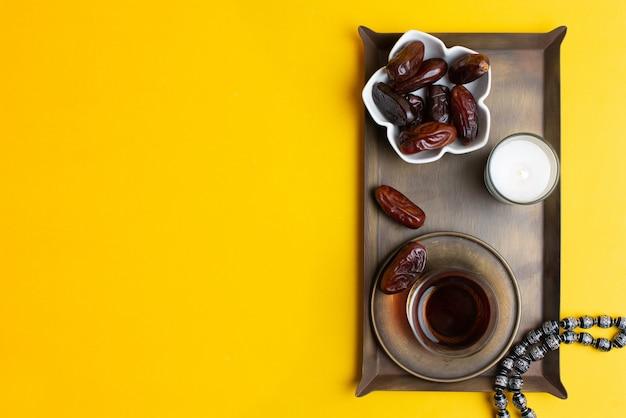 Ramadan kareem festival, nahaufnahme von datums bei schüssel mit rosenkranz und tasse schwarzen tee Premium Fotos