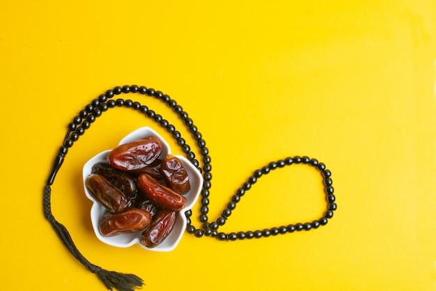 Ramadan kareem festival, termine an der schüssel mit rosenbeet auf gelbem hintergrund Premium Fotos
