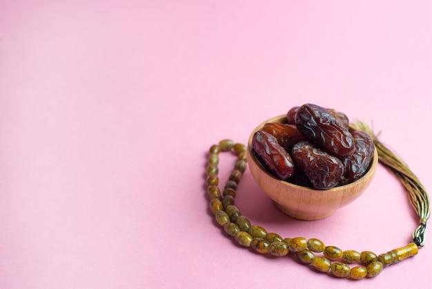 Ramadan kareem festival, termine an der schüssel mit rosenbeet auf rosa hintergrund Premium Fotos