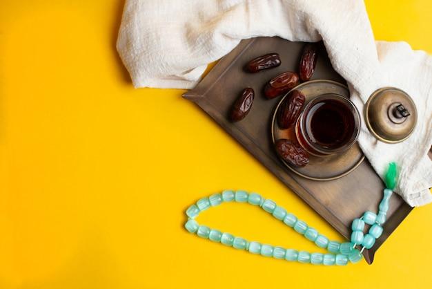 Ramadan kareem festival, termine auf holzschale mit tasse schwarzem tee und rosenbeet Premium Fotos