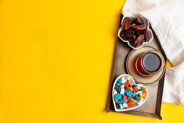 Ramadan kareem festival, termine auf schüssel mit tasse schwarzem tee und bunten süßigkeiten Premium Fotos