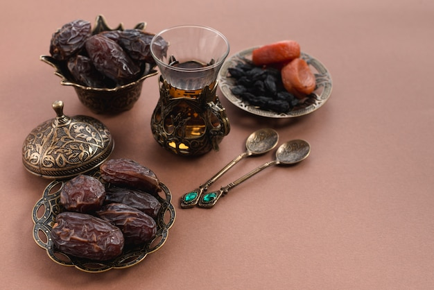 Ramadan kareem mit teeglas; premium-datteln und arabische trockenfrüchte auf braunem hintergrund Kostenlose Fotos