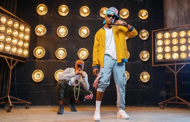 Rapper in mützen tanzen mit scheinwerfern auf der bühne Premium Fotos