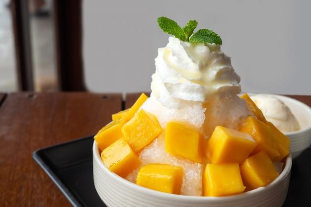 Rasierter eisnachtisch mit der mango geschnitten. serviert mit vanilleeis und schlagsahne. Premium Fotos