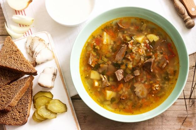 Rassolnik, traditionelle russische suppe, serviert mit verschiedenen snacks und wodka. Premium Fotos