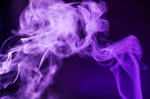 Rauchen sie auf einem dunklen hintergrund in einem hellen modischen lila neonlicht. Premium Fotos