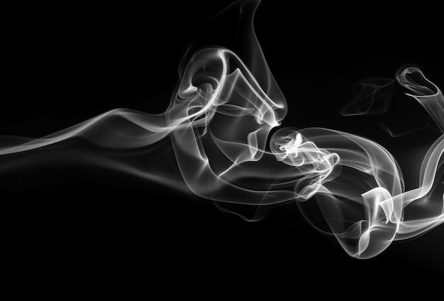 Rauchen sie den weißen weihrauch auf einem schwarzen hintergrund. dunkelheitskonzept Premium Fotos