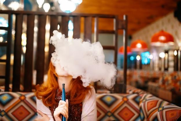 Rauchende huka der jungen frau im restaurant Premium Fotos