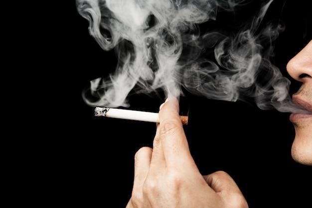 Rauchende zigarette des mannes im dunklen schwarzen hintergrund, welt kein tabaktageshalt rauch Premium Fotos