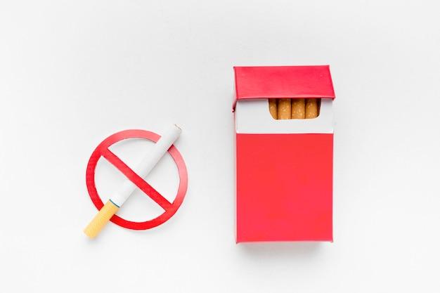 Raucherentwöhnungsschild neben zigarettenschachtel Kostenlose Fotos