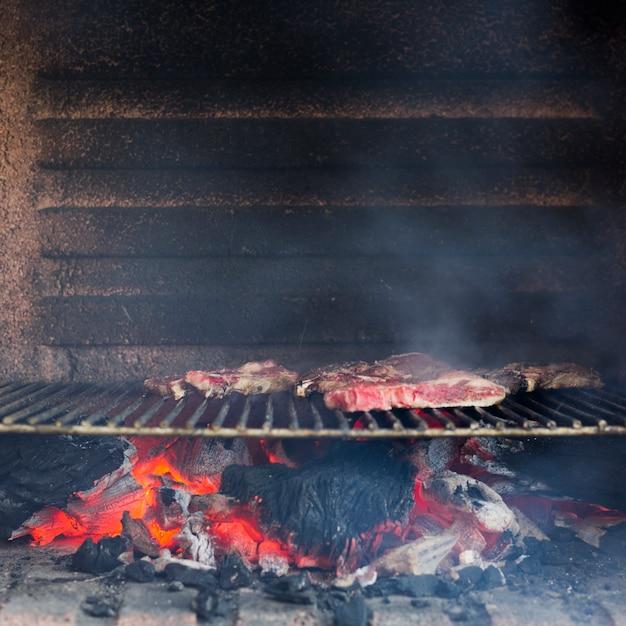 Rauchiges gegrilltes fleisch auf gebackener blechtafel im grill Kostenlose Fotos