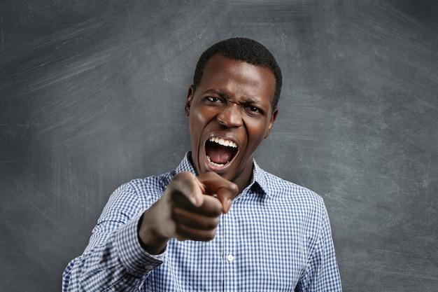 Raus aus dem unterricht! kopfschuss eines wütenden, wütenden, jungen, dunkelhäutigen lehrers, der schreit und auf seinen ungehorsamen schüler zeigt, wütend auf sein fehlverhalten, ihn schreit und tadelt. Kostenlose Fotos