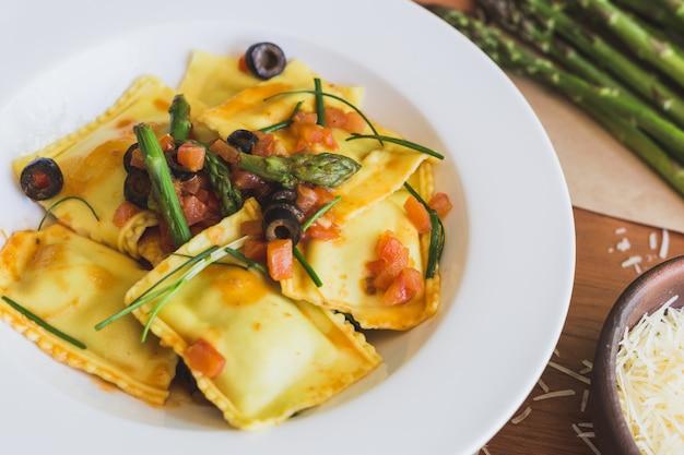 Ravioli mit oliven, spargel und tomaten hautnah Premium Fotos