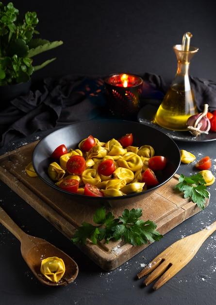 Ravioli mit tomaten auf schwarzblech in der rustikalen selbst gemachten lebensmittelumwelt, vogelperspektive Premium Fotos