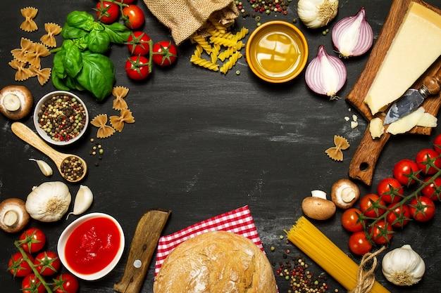 Raw Pasta mit Tomaten und Käse auf einem schwarzen Tisch einen Kreis zu machen Premium Fotos