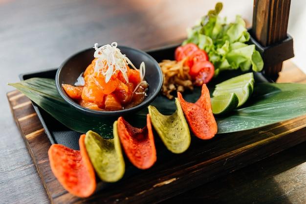 Raw salmon spicy salad serviert mit roten und grünen knusprigen chips für canape. Premium Fotos