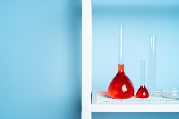 Reagenzgläser mit roter flüssigkeit im labor auf blau Premium Fotos