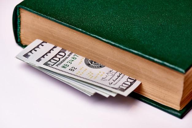 Rechnungen wert hundert us-dollars im buch auf einem weißen hintergrundmakro. Premium Fotos
