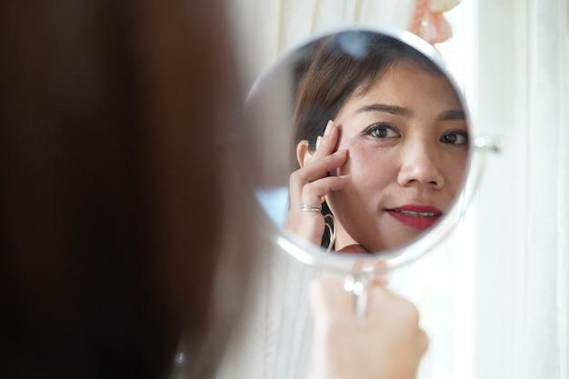 Recht asiatische frau, die spiegel nach der prüfung ihrer falte sucht Premium Fotos