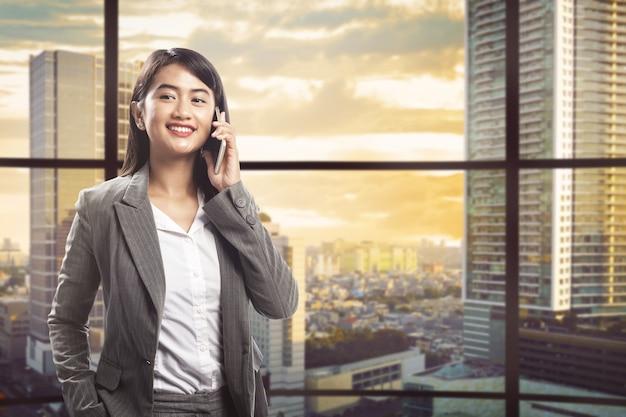 Recht asiatische geschäftsfrau, die auf smartphone spricht Premium Fotos