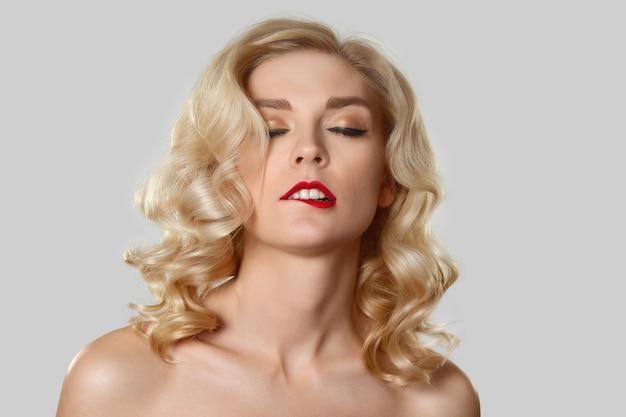 Recht blondes mädchen mit dem gewellten haar, katzenauge bilden das beißen ihrer roten lippen Premium Fotos