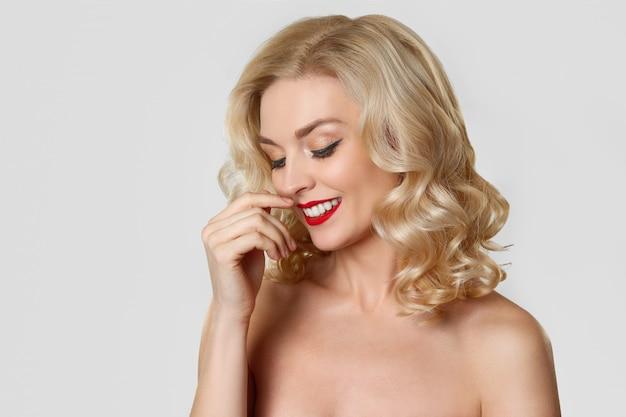 Recht blondes mädchen mit katzenauge bilden und die roten lippen, die ihr gewelltes haar berühren Premium Fotos