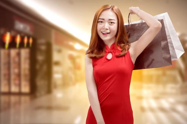 Recht chinesische frau in tragenden einkaufstaschen des traditionellen kleides Premium Fotos