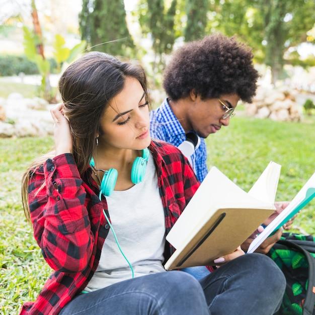 Recht entspannte junge frau, die ein buch mit seinem freund am rasen liest Kostenlose Fotos