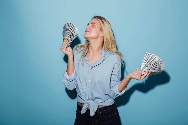 Recht junge erstaunliche blondine, die geld in den händen halten. Kostenlose Fotos