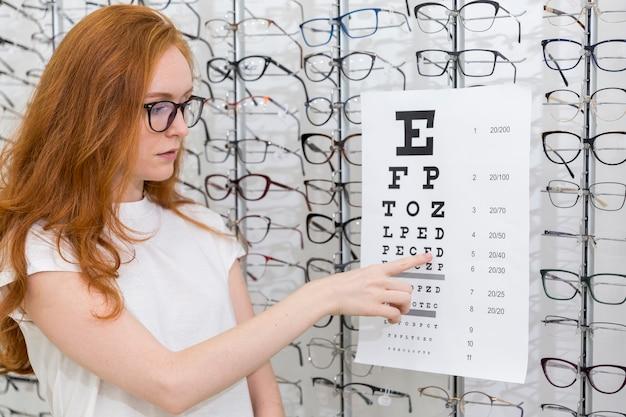 Recht junge frau, die buchstaben auf snellen diagramm im optikshop zeigt Kostenlose Fotos