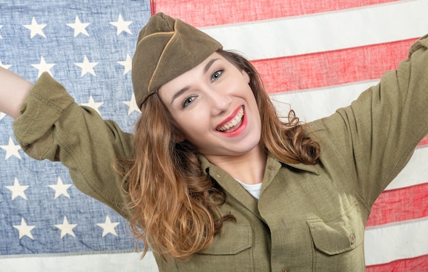 Recht junge frau in wwii-uniform wir mit amerikanischer flagge Premium Fotos