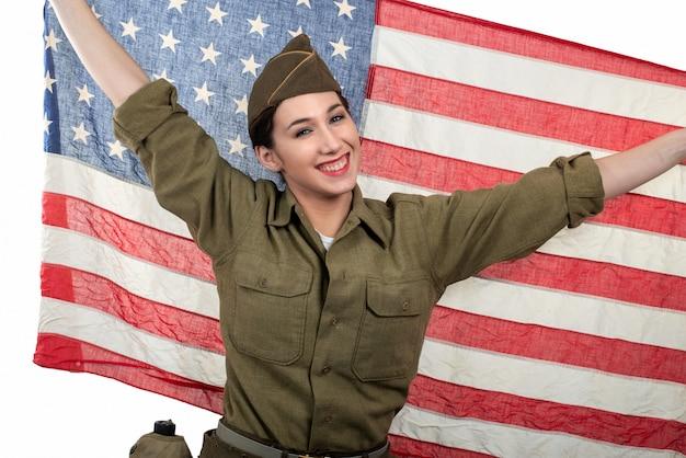 Recht junge frau in wwii-uniform wir mit einer amerikanischen flagge Premium Fotos