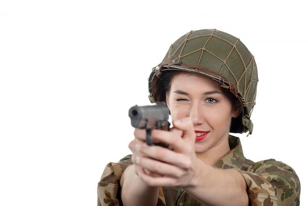 Recht junge frau kleidete in der amerikanischen militäruniform ww2 mit sturzhelm und pistole an Premium Fotos