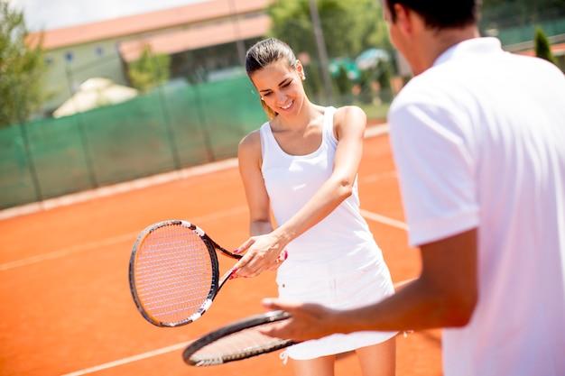 Recht junge frau mit ihrem übenden aufschlag des trainers auf tennisplatz im freien Premium Fotos