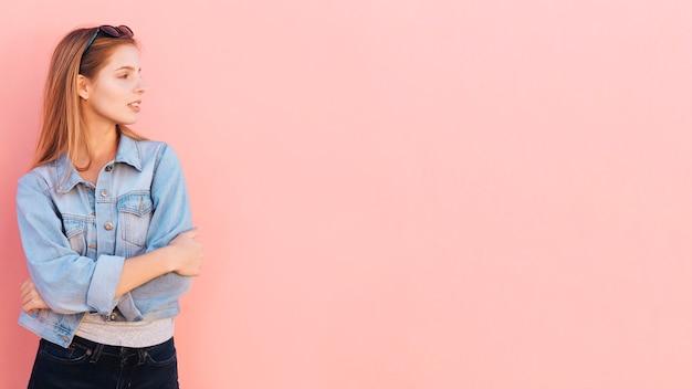 Recht junge frau mit ihren armen kreuzte das schauen weg gegen rosa hintergrund Kostenlose Fotos