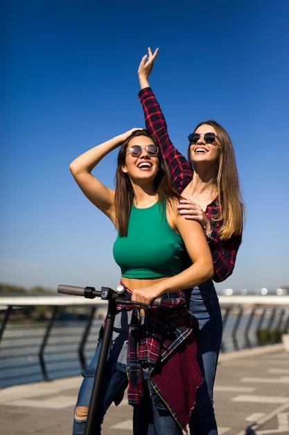 Recht junge freundinnen, die einen elektroroller in der straße reiten Premium Fotos