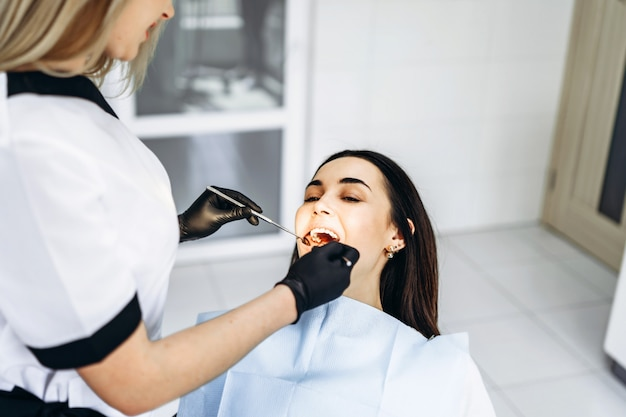 Recht junger weiblicher zahnarzt, der prüfung und behandlung für jungen weiblichen patienten in der zahnmedizinischen klinik macht. Premium Fotos