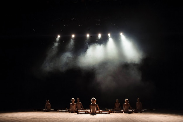 Recht junges mädchen, das auf dem stadium hat das ausdehnen und das training für balletttänze sitzt. Premium Fotos