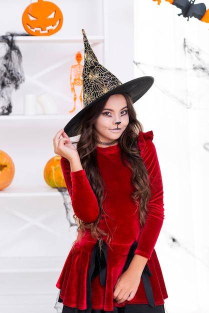 Recht junges mädchen, das im halloween-kostüm aufwirft Kostenlose Fotos