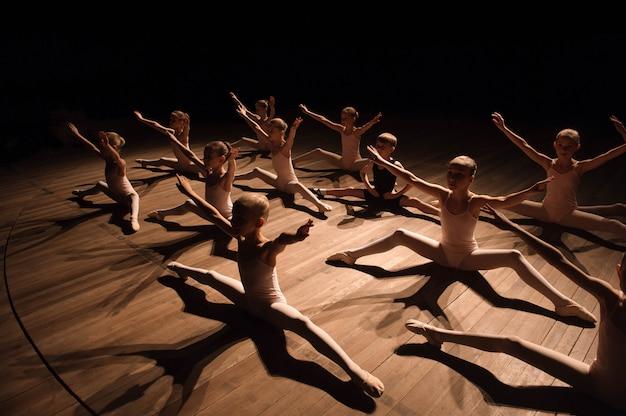 Recht junges mädchen und junge, die auf dem stadium hat das ausdehnen und das training für balletttänze sitzt. Premium Fotos