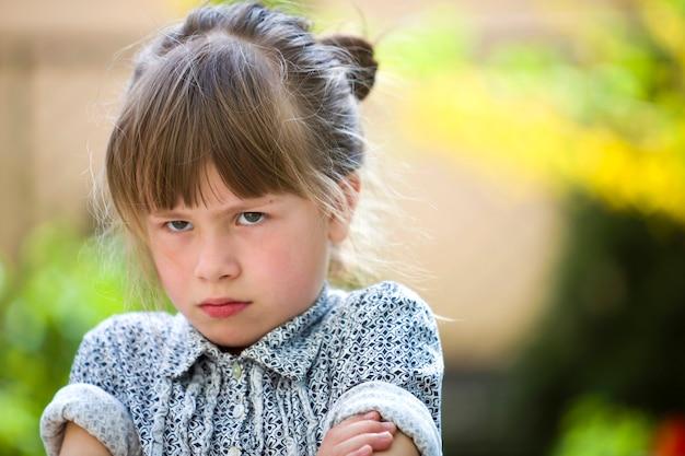 Recht lustiges schwermütiges kleinkindmädchen im freien, das auf unscharfem sommergrün verärgert und unbefriedigt sich fühlt. kinder wutanfall. Premium Fotos