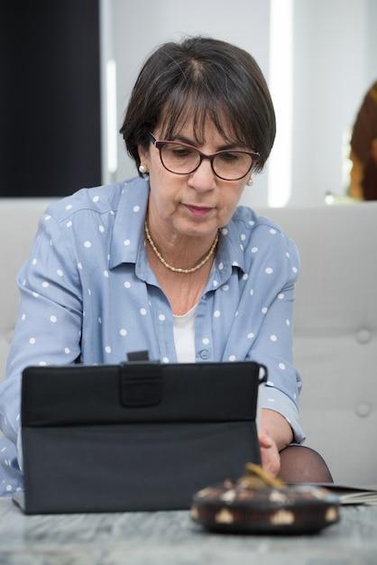 Recht reife frau, die zu hause tablet-computer verwendet Premium Fotos