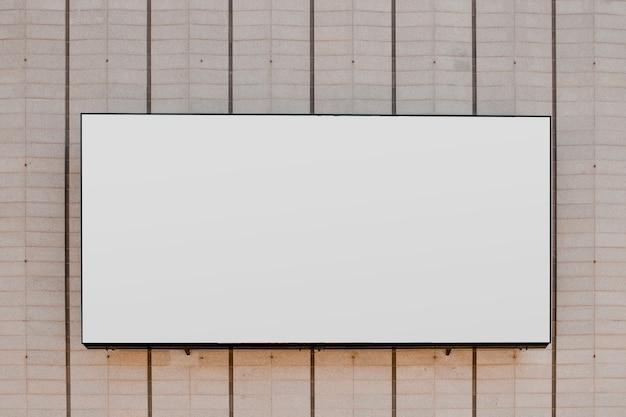 Rechteckige weiße leere anschlagtafel auf gestreifter wand Kostenlose Fotos