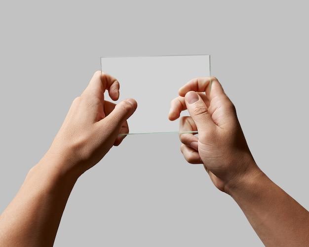 Rechteckiges transparentes glas in den männlichen händen auf einem grauen hintergrundplatz für text Premium Fotos
