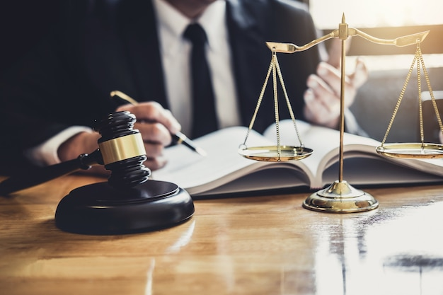 Rechtsanwalt oder richter, der mit vertragspapieren, gesetzesbüchern und hölzernem hammer auf tisch arbeitet Premium Fotos