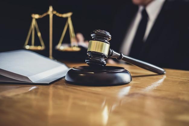 Rechtsanwalt oder richter, die mit vertragspapieren, gesetzbüchern und hölzernem hammer auf tabelle im gerichtssaal arbeiten Premium Fotos