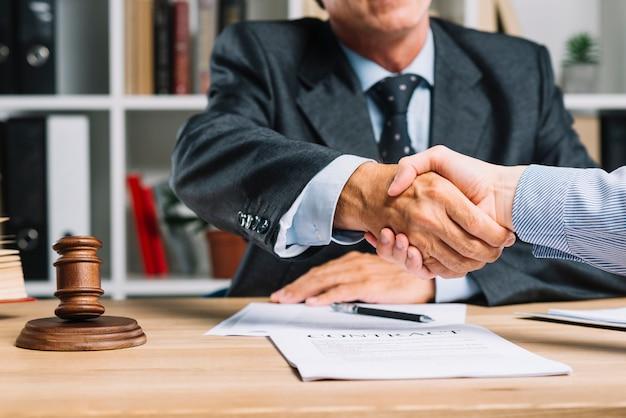 Rechtsanwalt und sein klient, die hände über dem schreibtisch zusammen schütteln Kostenlose Fotos