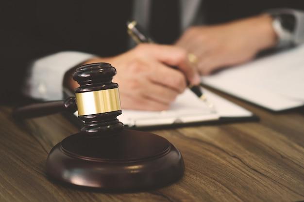 Rechtsanwalts- / richterhammer, der mit rechtsdokumenten in einem gerichtssaal arbeitet Premium Fotos